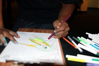 Ivan Garcia, 22, works on a drawing at a fundraising event for the alley activation project.