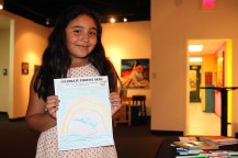 Tori Villa, 10, poses with her picture celebrating Pheonix arts at a fundrasing event for the alley mural project.