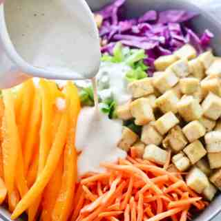 Pouring dressing onto asian tofu crunch salad