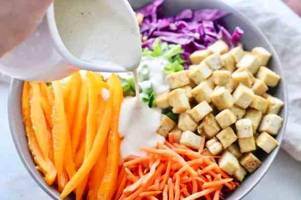 Pouring dressing onto asian tofu crunch salad