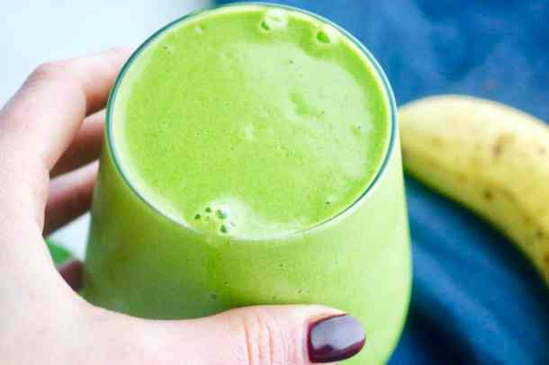Hand holding glass green smoothie
