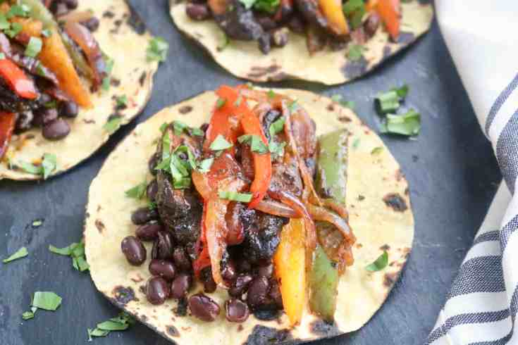 Hearty black beans, taco seasoned mushrooms, onions and peppers on top of perfectly charred corn tortillas topped with fresh cilantro and homemade guacamole. Vegan, Vegetarian, gluten-free. Easy make-ahead meal, perfect meal prep recipe! Ready in under 30 minutes! #blackbeanveggiefajitas, #portobellomushrooms, #veganfajitas, #vegetarian, #glutenfreerecipe, #mealpreprecipe, #guacamole,