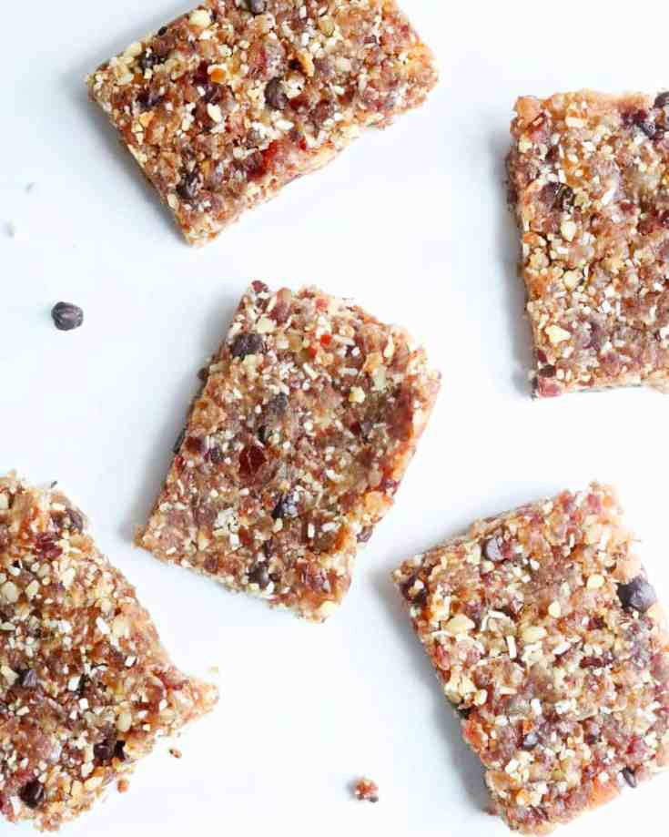 Healthy sweet dates mixed with dried fruit, walnuts, shredded coconut and dark chocolate chips. These No Bake Energy Bars are made in 3 steps and require no baking. They are nice and chewy with the perfect hint of sweetness and will give you enough energy to power through your day! Vegan and Gluten-Free! #energybars #nobakedesserts #easyenergybars #dates #walnuts