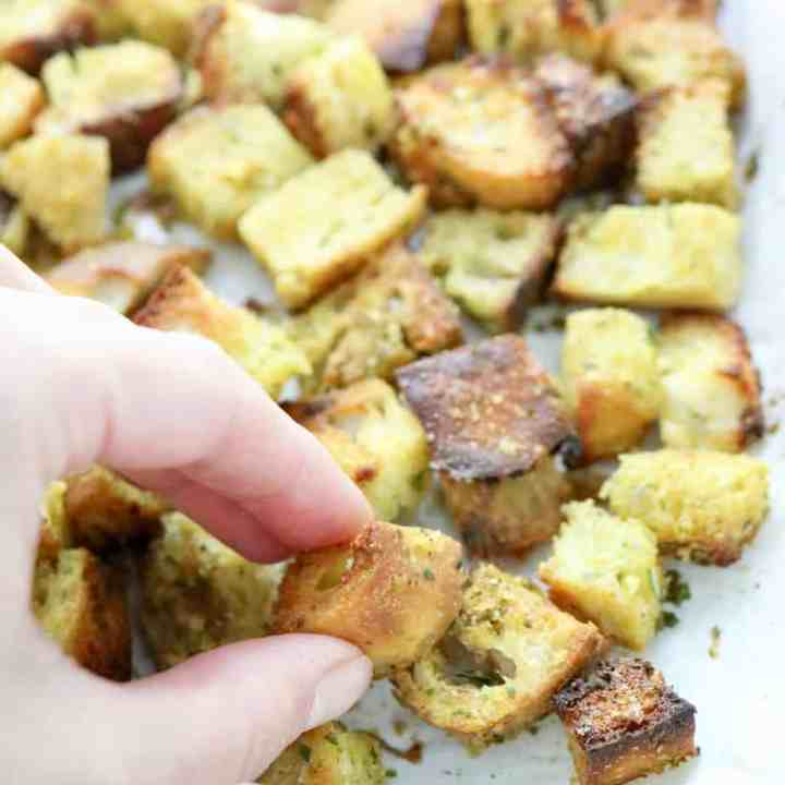 Hand grabbing crouton from pan