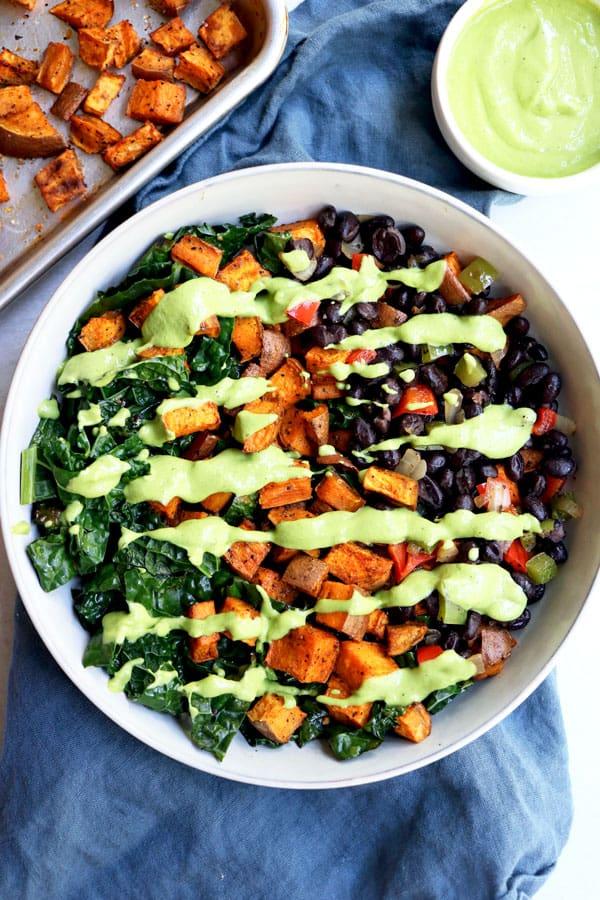 Overhead shot of vegan sweet potato buddha bowl with avocado drizzle