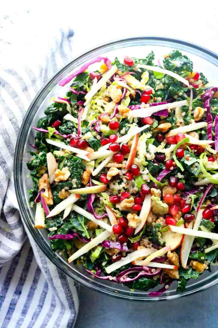 Hearty green kale mixed with fluffy quinoa, Brussel sprouts, crisp apples, tart pomegranate seeds, shaved red onion, and walnuts all tossed in a tangy, slightly sweet mustard vinaigrette dressing.  Vegan, gluten-free and a perfect make-ahead lunch or dinner! #kalesalads #kale #easymakeaheadsalad