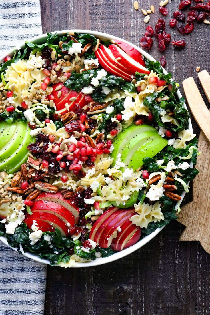 An easy Autumn Crunch Pasta Salad to use all of those wonderful fall fruits and veggies.  Colorful, crunchy, packed with flavor and so good, you will want to eat it every day!  Fluffy pasta, tart crisp apples, and pears nestled in a bed of dark leafy kale and Brussel sprouts and topped with nuts and feta cheese.  Dressed all up with olive oil, vinegar, lemon, and honey. #easykalesalads #kalesaladrecipes #fallsalads #kalerecipes
