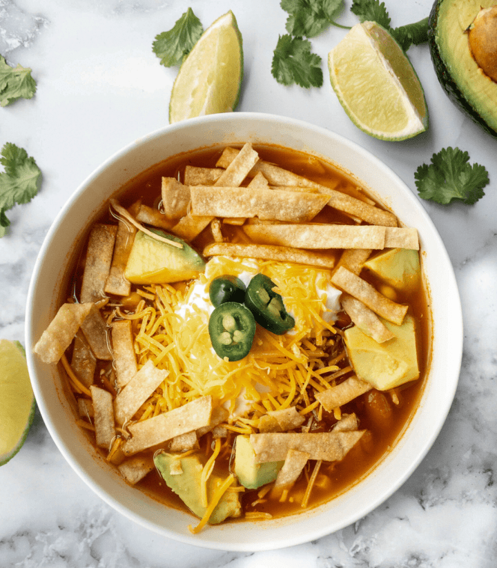 bowl filled with chicken tortilla soup topped with tortillas, cheese and jalapenos