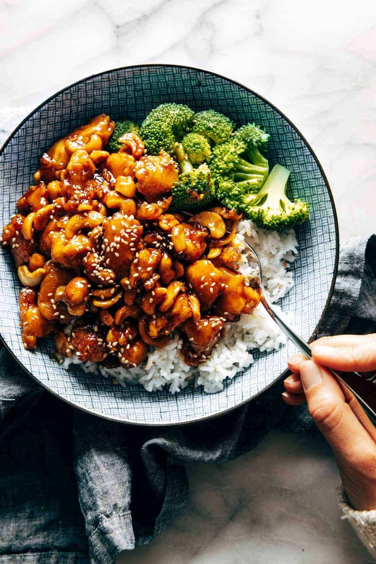 Cashew chicken in a bowl with rice and broccoli.