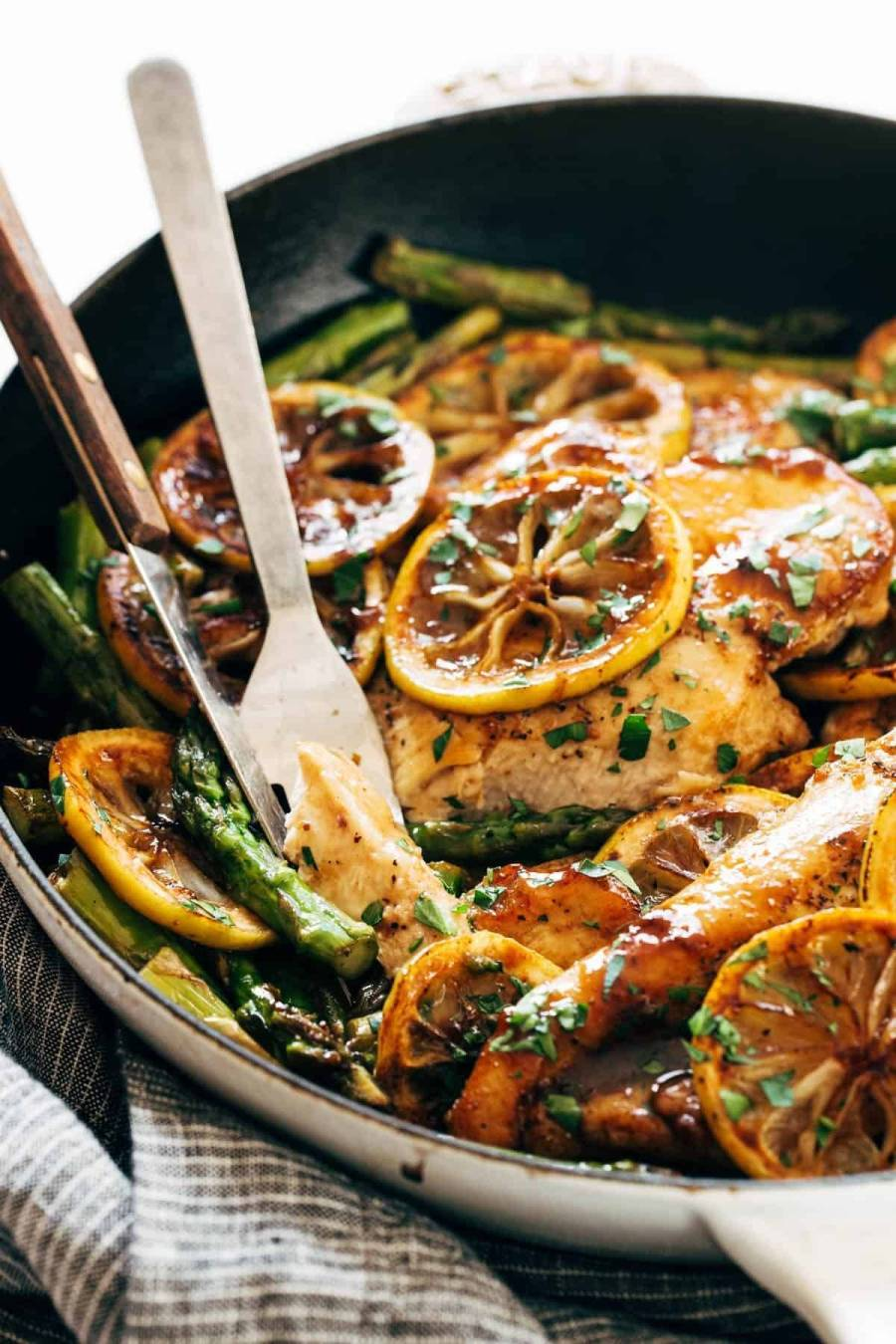 Lemon chicken with asparagus in a pan with a fork