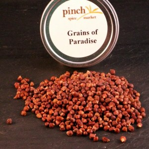 tin of grains of paradise with pile next to it