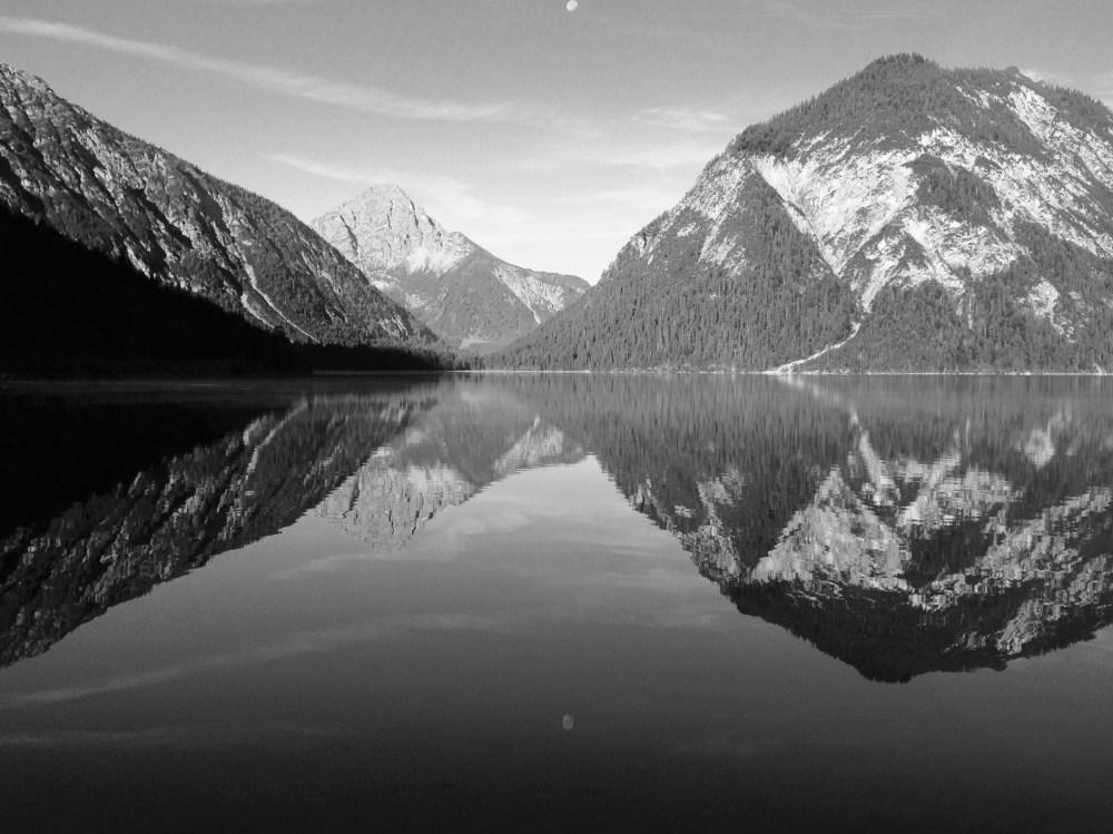 Im Plansee spiegeln sich die umliegenden Berge.