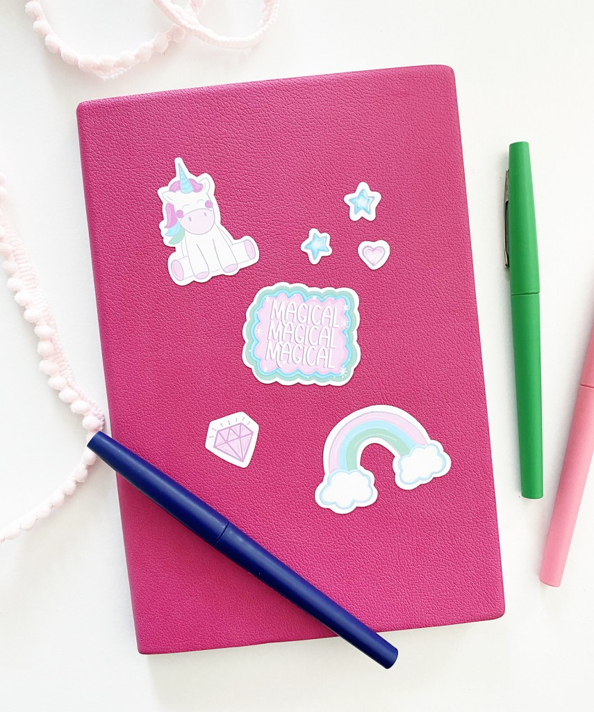 Free Printable Unicorn Stickers on a Pink Notebook