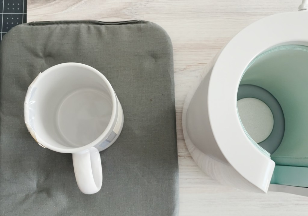 Sublimation Mug Cooling on Cricut Heating Mat next to Cricut Mug Press