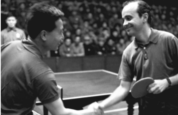 Yang Ruihua (L) shaking hands with US Dick Miles before the friendship match