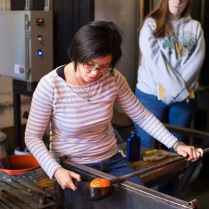 Helen Lee using a wooden block to shape a gather of hot glass