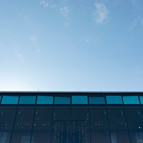 "Image of ""Cloud Text"" taken from the ground level of the Chazen Museum of Art. The panels of the piece are reflecting the clouds in the sky with different shades of blue."