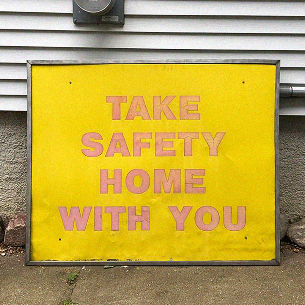 "Found signage that reads ""TAKE SAFETY HOME WITH YOU"" in bold pink letters over a yellow background."