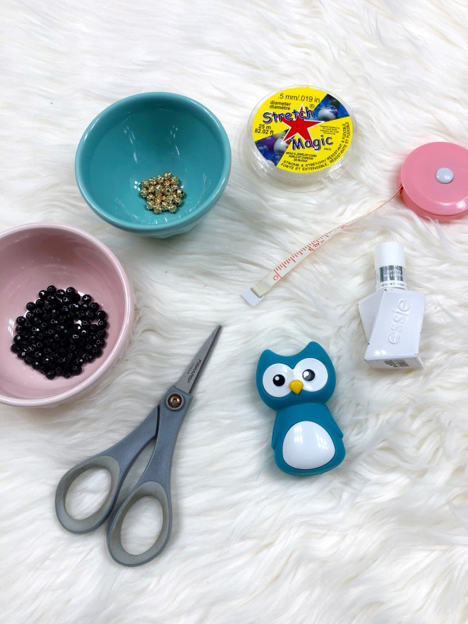 Beading supplies including bowls of glass beads and gold spacers along with elastic cord, a tape measure, scissors, clear nail polish, and a chip clip - Pink Bows & Twinkle Toes