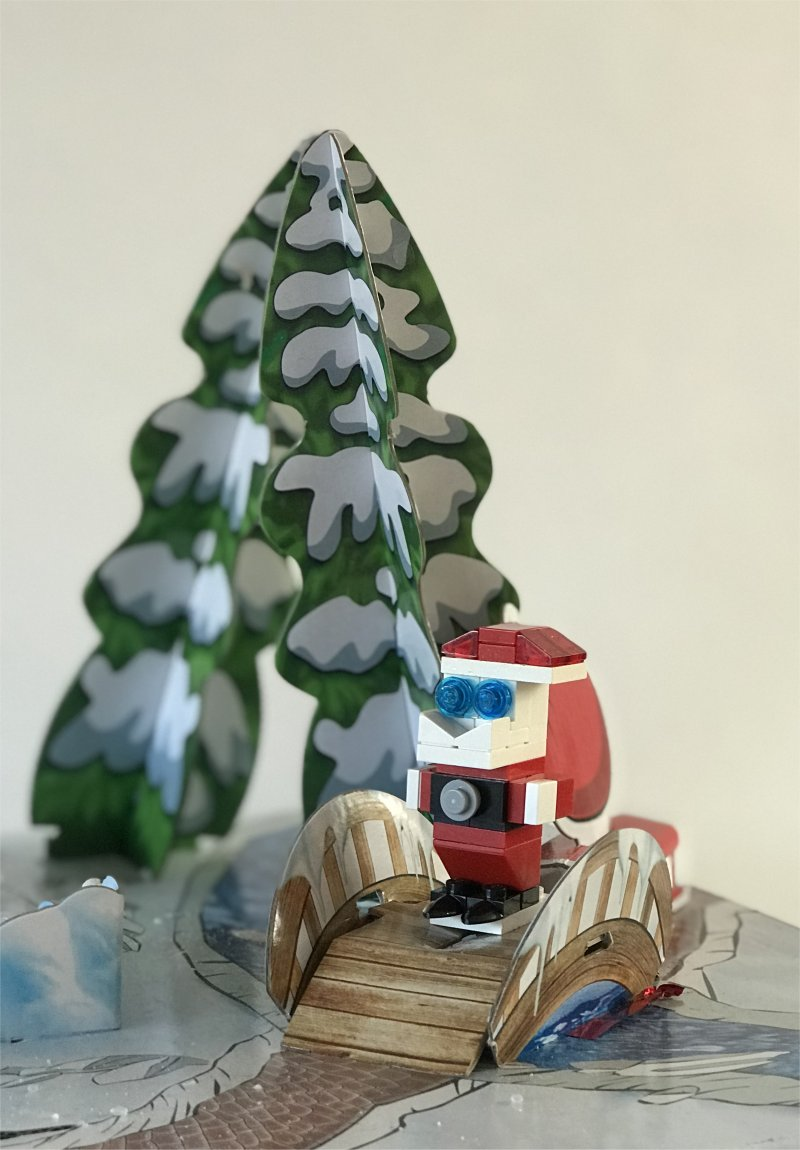 lego father christmas on a bridge with a snow covered christmas tree in the background