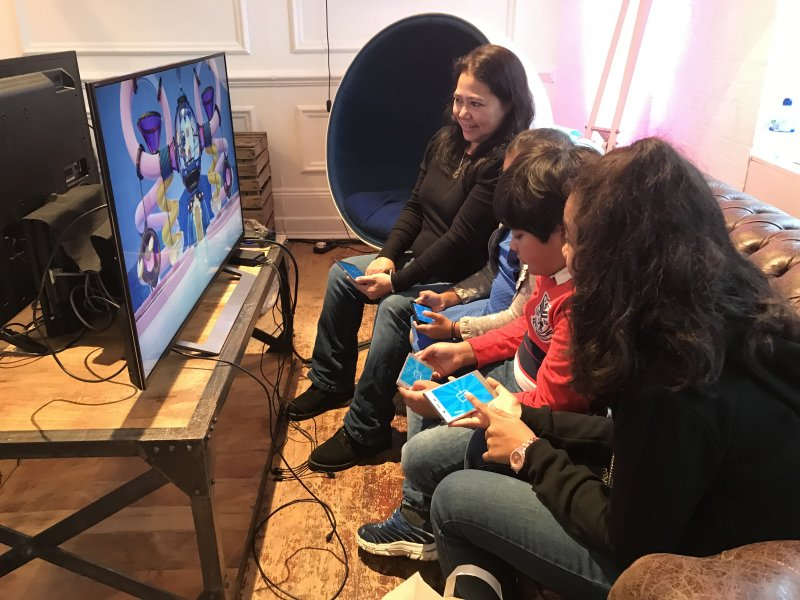 Family playing Playlink with Playstation in front of the television