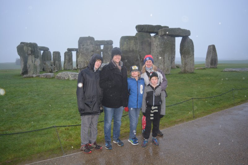 family standing in front of stone circle at stonehenge