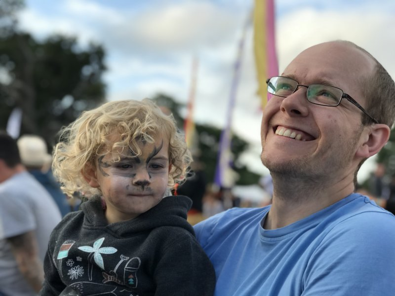 man and child with facepaint enjoying festival