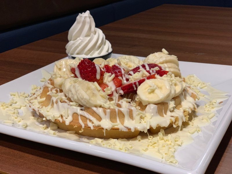 waffle with strawberries and bananas dripped in white chocolate and ice-cream