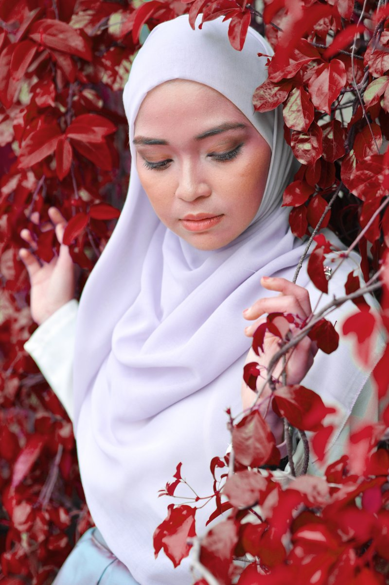 Muslim lady in white surrounded by red leaves