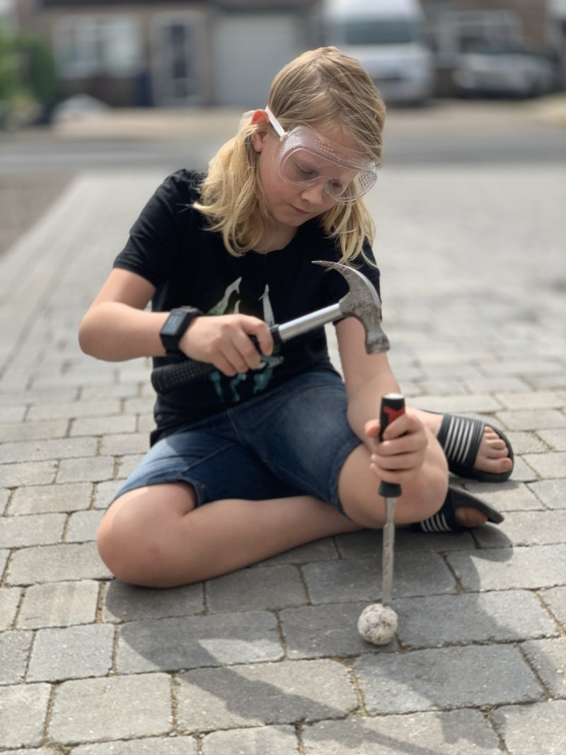 Boy with long blonde hair wearing goggles opening a geode with a hammer and chisel