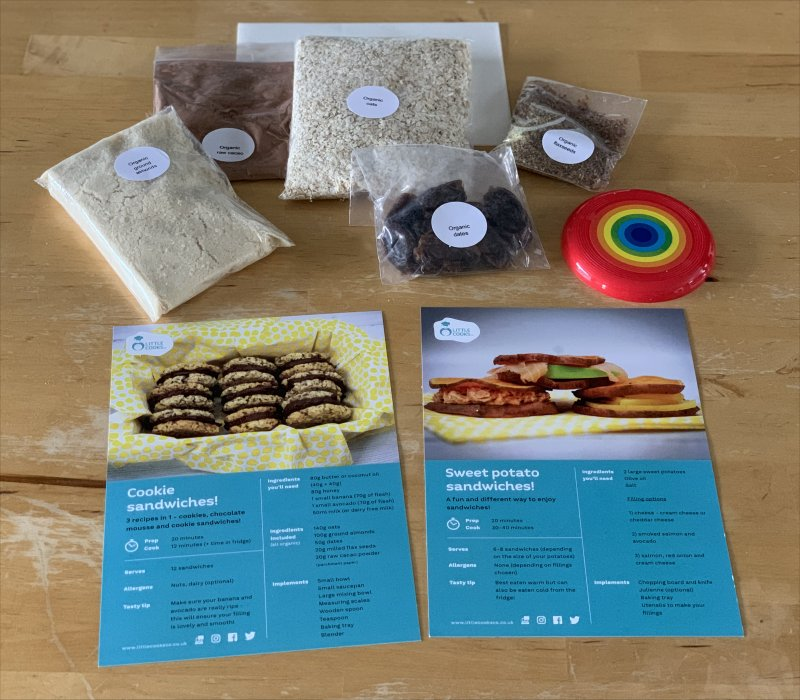 Contents of the Little Cooks Co Subscription box - including 2 recipe cards, dry ingredients and a plastic rainbow disk
