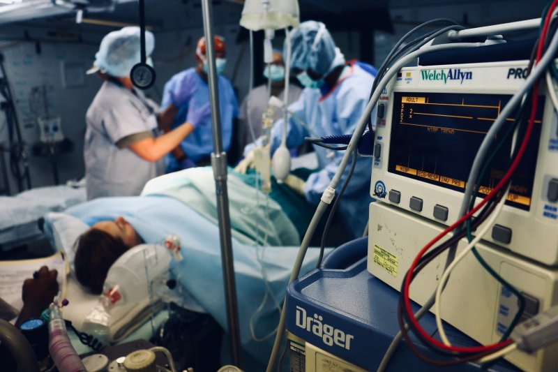woman surrounded by medics on hospital bed