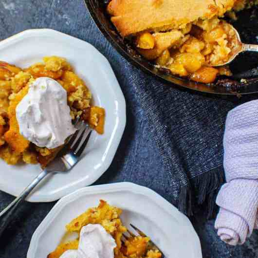 cornbread skillet peach cobbler in cast iron skillet with two servings on small plates