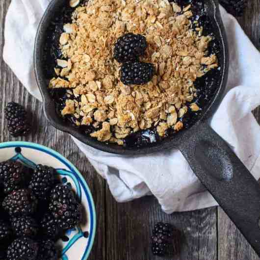 blackberry crumble with oat topping served in a 6-inch cast iron skillet topped with fresh blackberries.