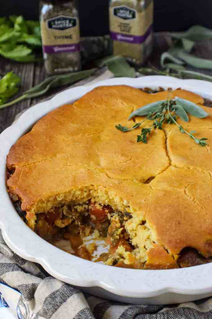 Cornbread Vegetable Pot Pie in a glass pie dish garnished with fresh herbs on top of striped linen on wood surface with a wooden spoon and vegetables around the pie dish