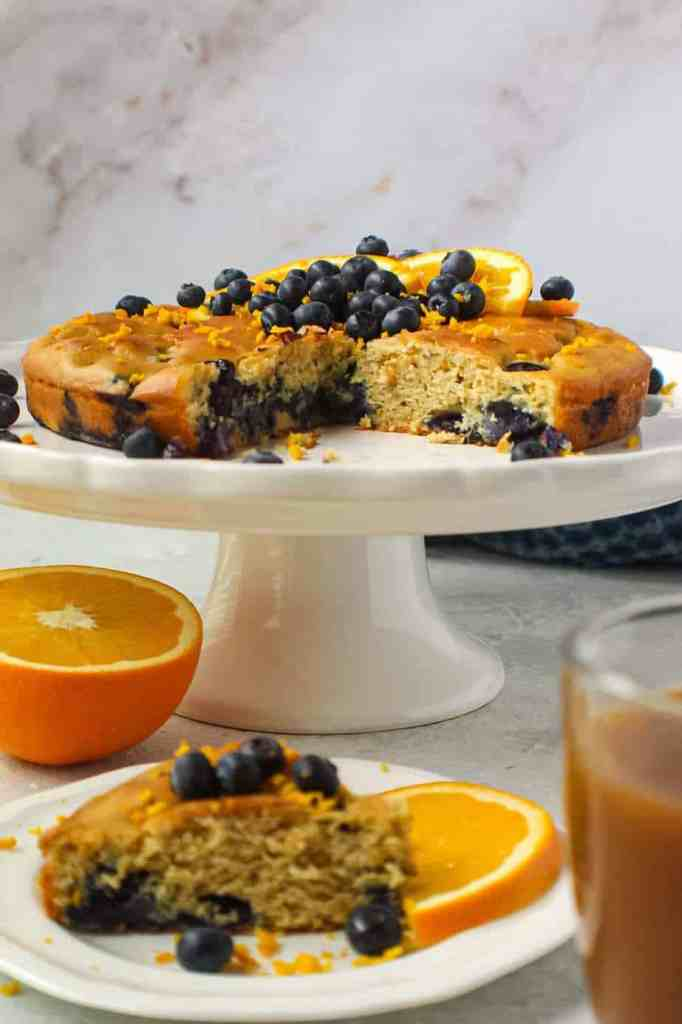 side angle shot of orange blueberry breakfast cake on white cake stand with fresh blueberries on top and garnished with fresh orange slices and orange zest. Half an orange and blue towel in the background.y breakfast cake