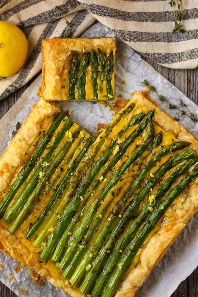 overhead shot of asparagus puff pastry tart with gouda with a corner slice cut out on parchment paper on top of wooden surface.