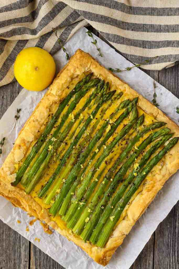 overhead shot of asparagus tart on wooden surface with half a lemon a striped linen in perimeter of shot
