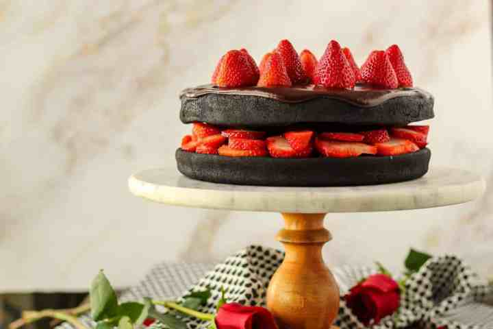 side angle shot of dark chocolate strawberry cake with chocolate ganache on top of marble and wood cake stand with cloth napkin and roses in background.