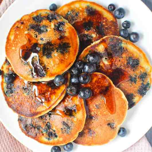 overhead shot of almond flour pancakes on white dinner plate with fresh blueberries