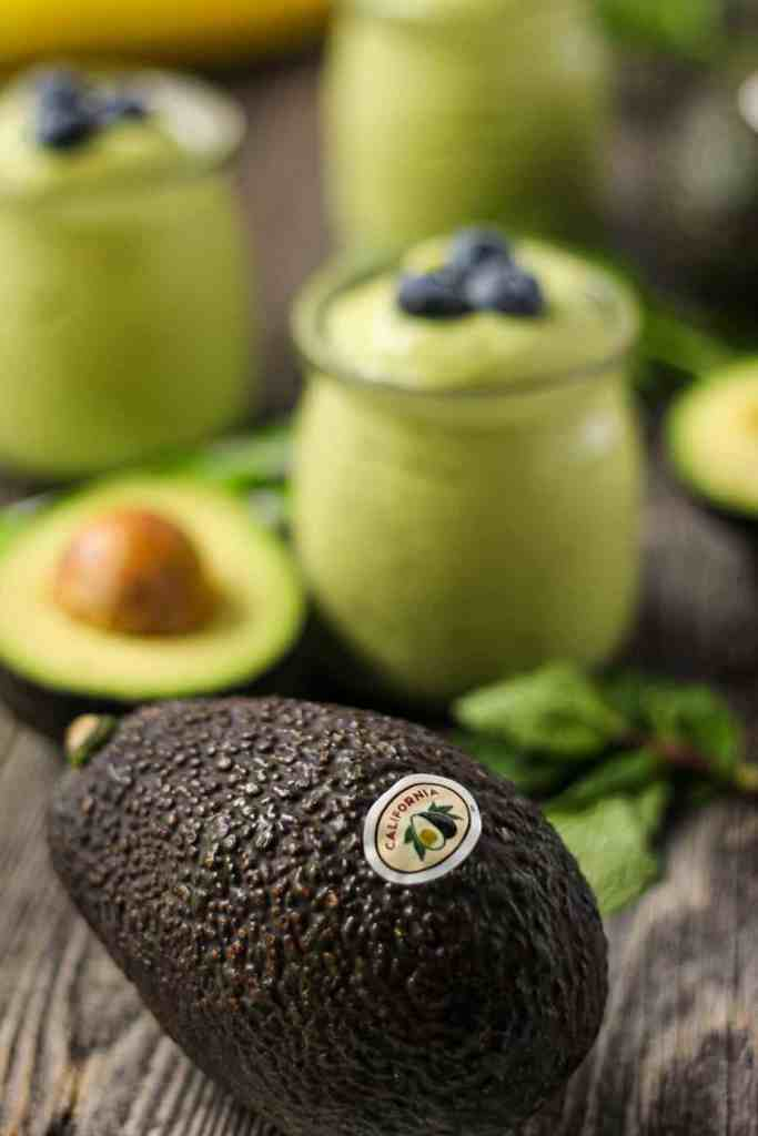 avocado smoothies in clear glasses on wood surface with a whole avocado in front of shot