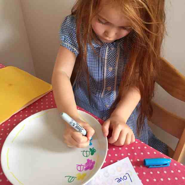 Ava decorating a plate with Sharpie pens