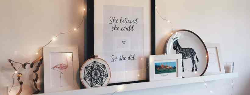 White shelf with pictures and copper fairy light