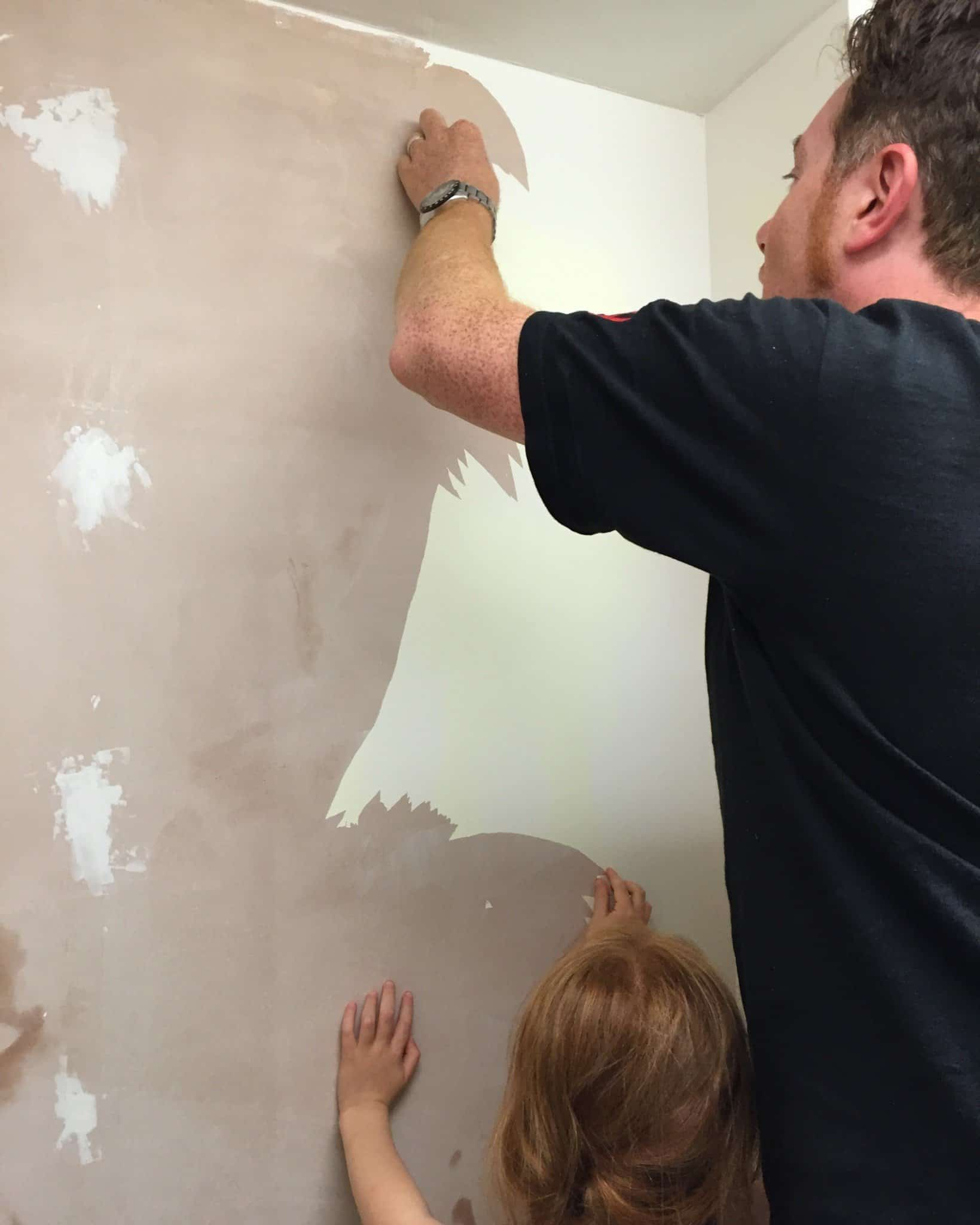 Ryan and Ava peeling old paint off the utility room wall