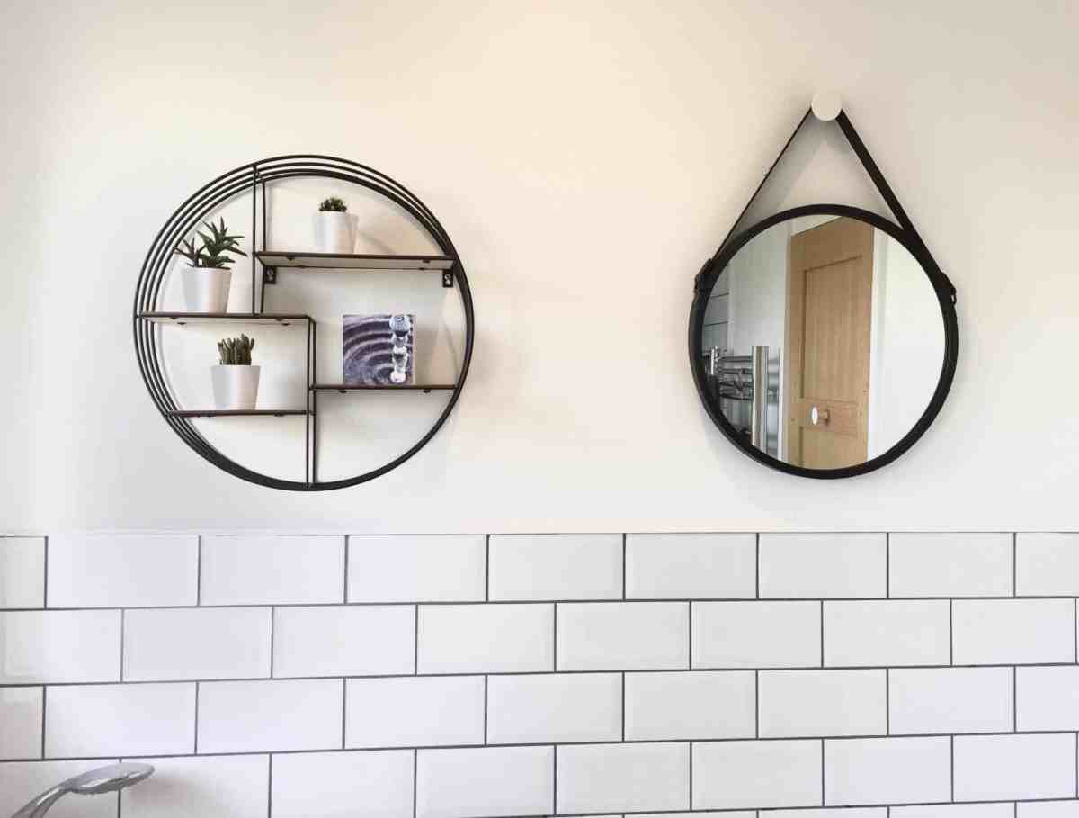 Black circular shelving and mirror in a monochrome family bathroom