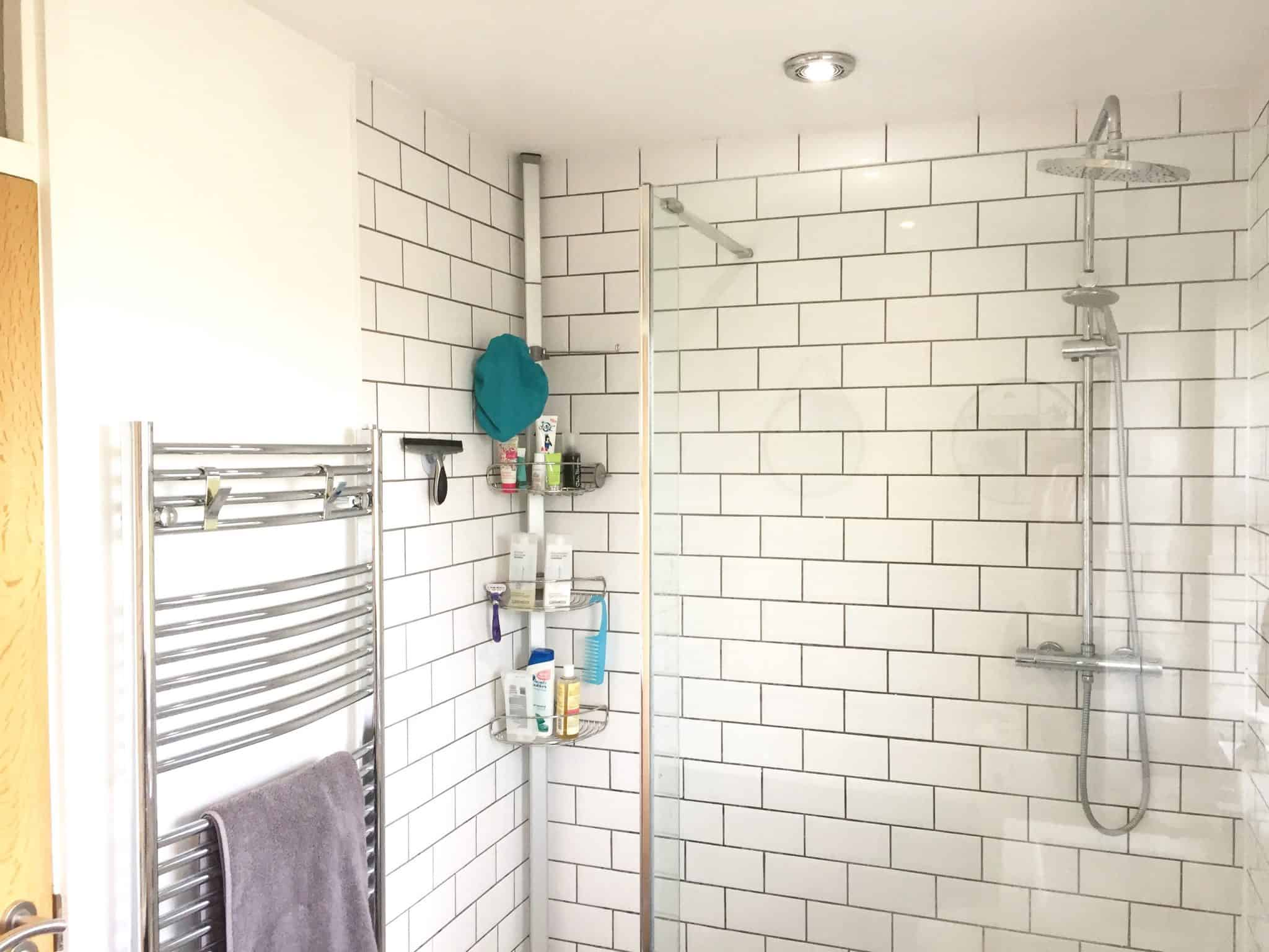 Walk in shower and chrome towel rail with monochrome tiles