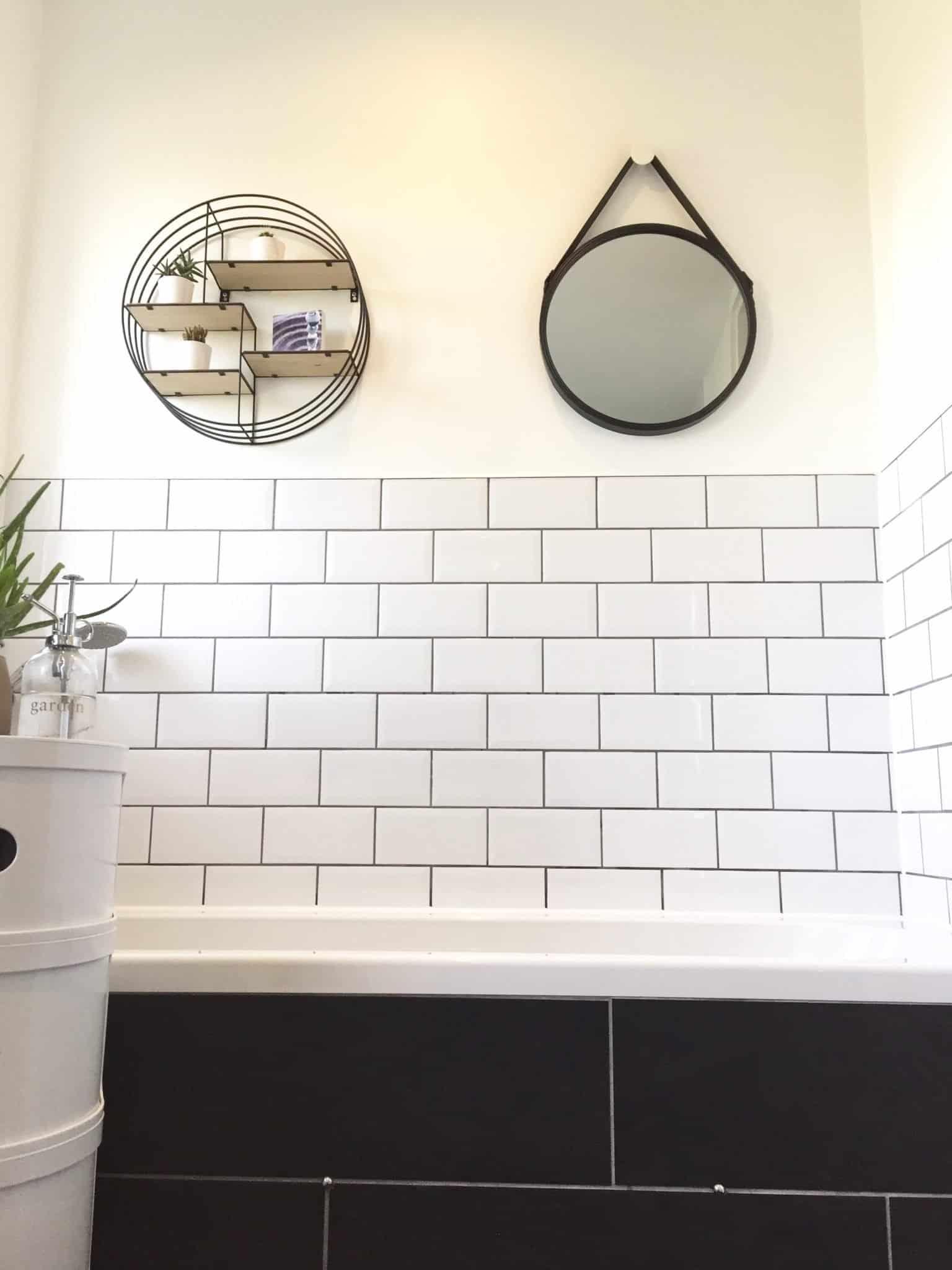 White metro tiles and grey grout, circular shelves and mirror