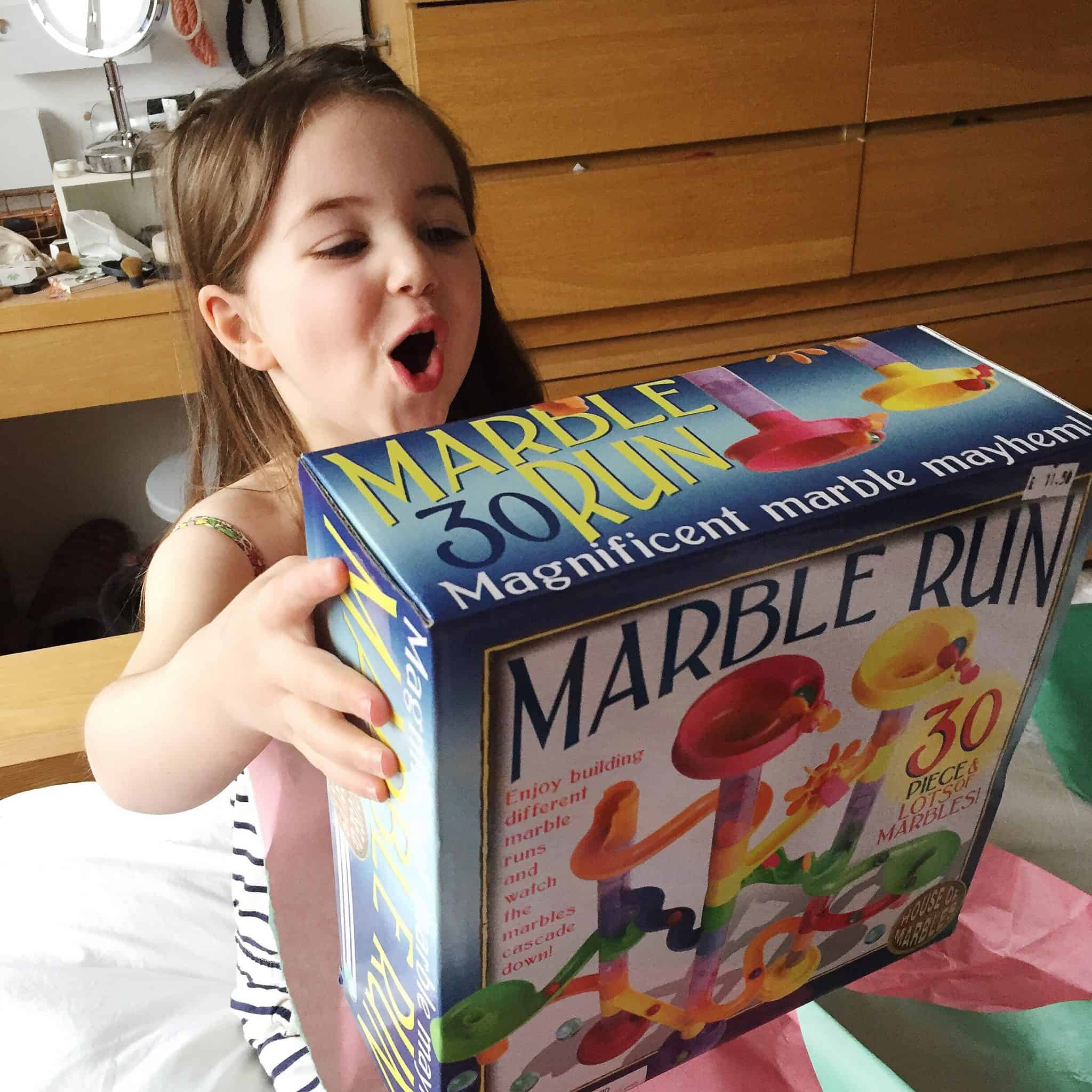 Thea on her 4th birthday opening her marble run