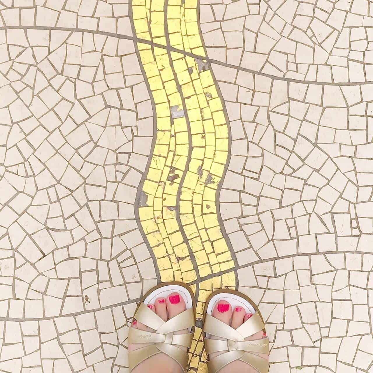 Original Gold Salt-Water Sandals on a gold moasic floor
