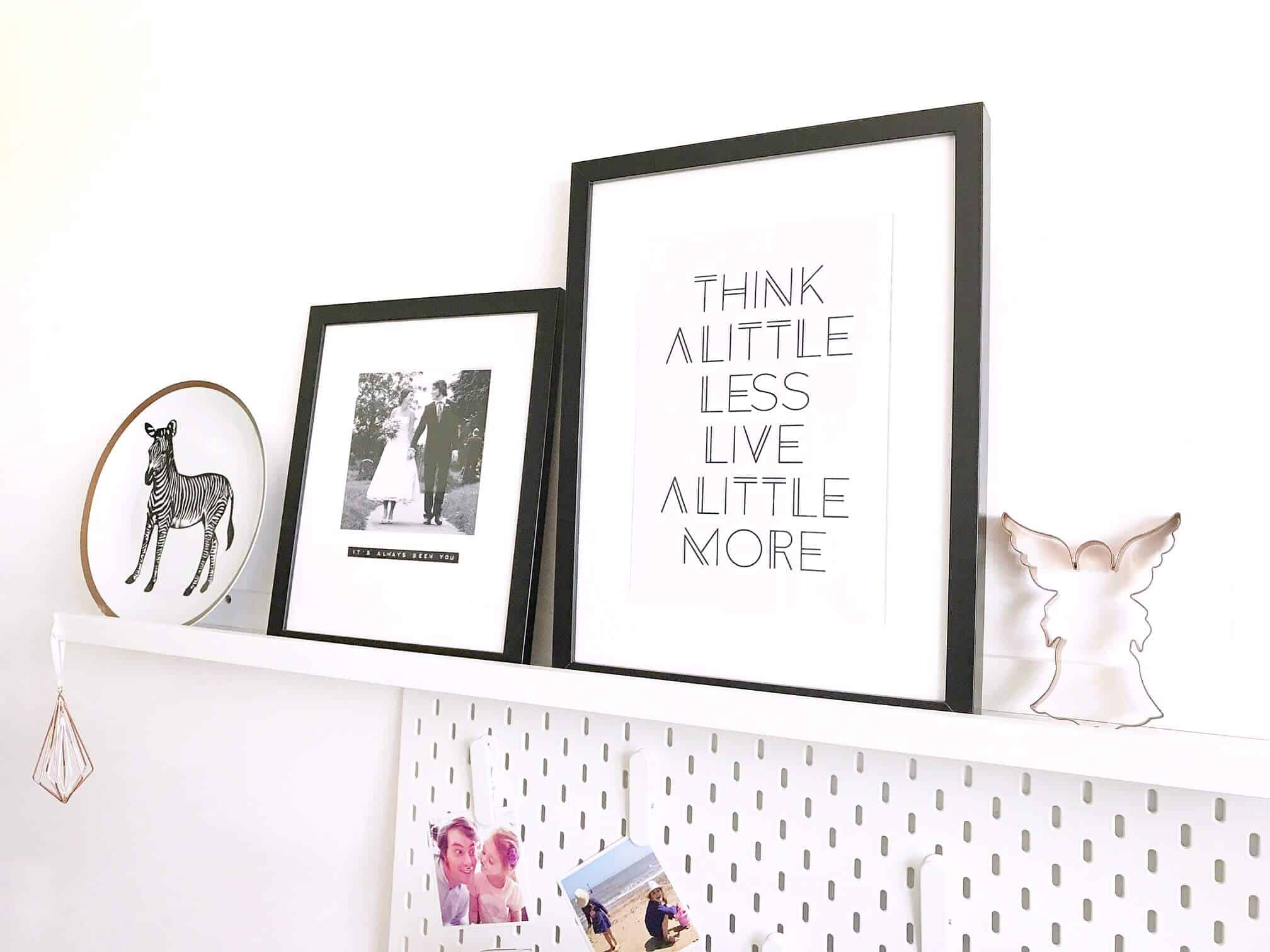 Think a Little Less, Live a Little More print on a white shelf